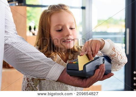 little female child paying with credit card in boutique