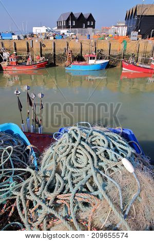 WHITSTABLE, UK - OCTOBER 15, 2017: Close-up on fishing nets at the fishing Harbor with fishing boats and wooden huts in the background