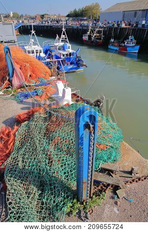 WHITSTABLE, UK - OCTOBER 15, 2017: The fishing Harbor with colorful fishing nets in the foreground