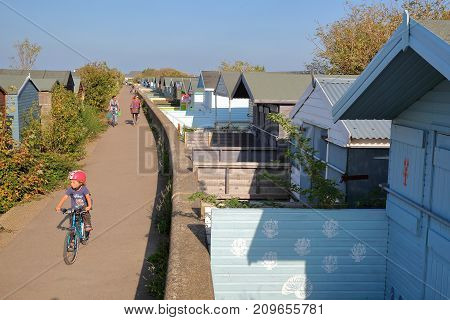 WHITSTABLE, UK - OCTOBER 15, 2017: A row of colorful wooden Huts along a pathway and overlooking the sea