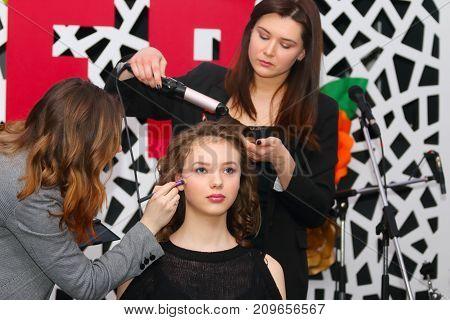 PERM RUSSIA - FEB 12 2017: Makeup artist hair stylist work with model at Wedding Fair Perm 2017