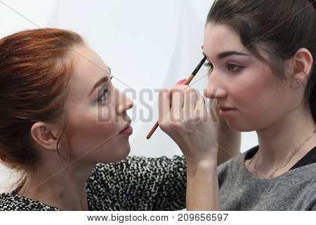 PERM RUSSIA - FEB 12 2017: Makeup artist (with model release) aligns eyebrow line for model at Wedding Fair Perm 2017