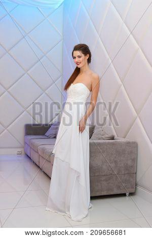 PERM RUSSIA - FEB 12 2017: Brunette bride in white dress poses near flowers wall at Wedding Fair Perm 2017