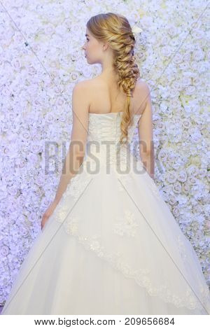 PERM RUSSIA - FEB 12 2017: (back view) Model bride in white dress poses near flowers wall at Wedding Fair Perm 2017