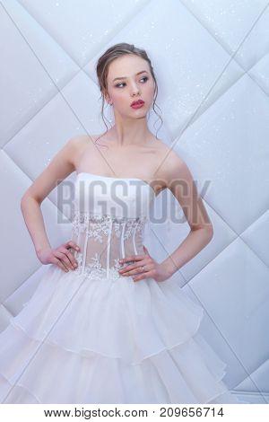 PERM RUSSIA - FEB 12 2017: Pretty model bride in white dress poses at Wedding Fair Perm 2017