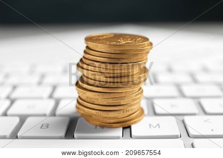 Stack of coins on white keyboard, closeup