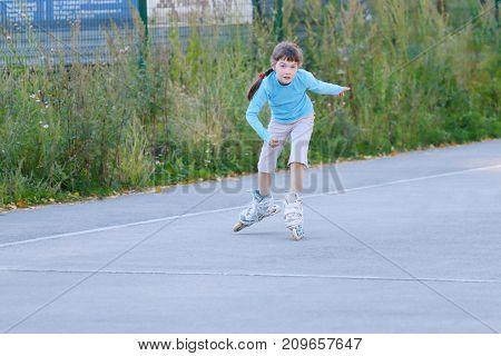 Happy girl roller skates on playground near green grass under at summer day