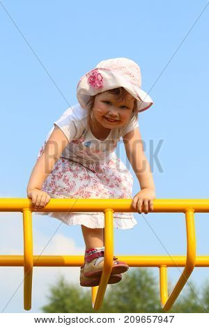 Little cute girl in hat climbs on children playground at sunny day