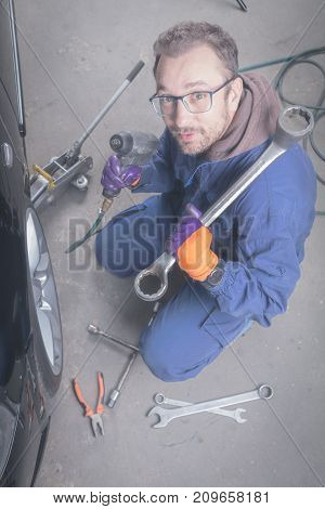 Car mechanic changing tire in the service - shop.