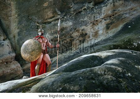 Full lengths shot of a Spartan warrior with sexy muscular strong athletic body standing near the rock wearing red cape holding a spear and a shield.