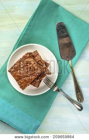 An overhead photo of a stack of brownies sprinkled with sugar, with a fork and a serving spoon, on teal textures with a place for text