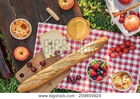 An overhead photo of a picnic with an apple, a bottle of rose wine, fresh cherries, a quiche, a corkscrew, and a piece of cheese, on a rustic wooden board on top of green grass, with a place for text