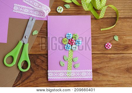 Beautiful greeting card on a wooden table. Greeting paper card for mom's birthday or mother's day or father's day. Kids workplace. Paper crafts for kids idea. Easy art and craft with paper. Top view