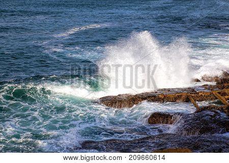 Sea waves crashing against the rocks .