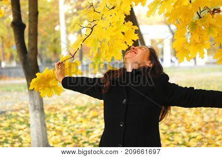 A Funny Young Attractive Girl Has Fun And Fooling Around In An Autumn Park. Cheerful Emotions, Autum