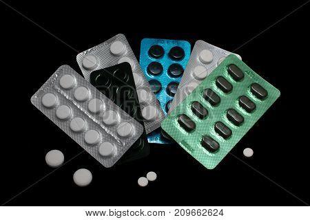 Pile of several medicines on black background