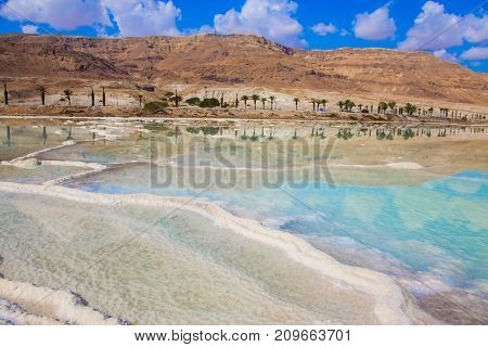 The concept of ecological tourism. The evaporated salt on the shallow coast of the Dead Sea, Israel
