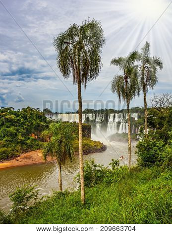 The tropical sun illuminates the seething waters. Waterfalls Iguazu. Picturesque basaltic ledges form the famous waterfalls. The concept of active and exotic tourism