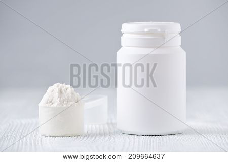 mock up bottle and a spoon with powder, selective focus, on gray background