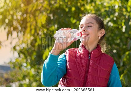 Beautiful girl drinking water after jogging in outdoor. A young beautiful girl is drinking water the hot sun, in the park. Healthily concept. Healthy lifestyle concept. copy space. Portrait girl