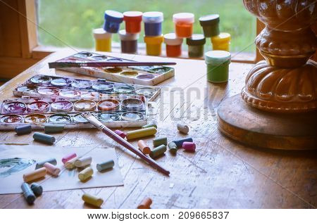 Old pastels crayons three palettes of different colors colorful paint tubes and artistic brush on vintage wooden background. Used tools for drawing and painting art. Visual arts concept.