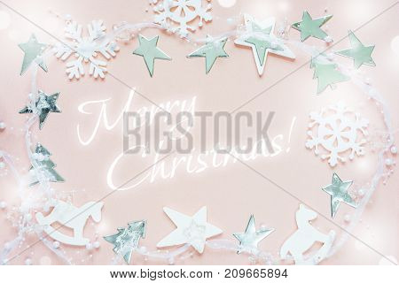 Christmas greeting card composed of white christmas decoration: snowflakes stars Christmas trees and toy; rocking horse on pink background with inscription Merry Christmas! Flat lay composition for greeting card websites social media magazines bloggers ar