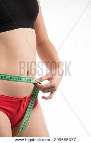 Girl with an apple on a diet measuring waist and abdomen centimeter and looks much fat