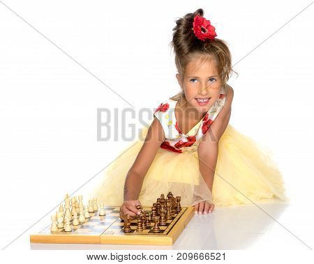 A little girl is playing chess. The concept of creative education of a child, training of thinking. Isolated on white background