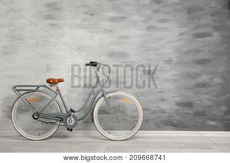 Retro bicycle near grey wall