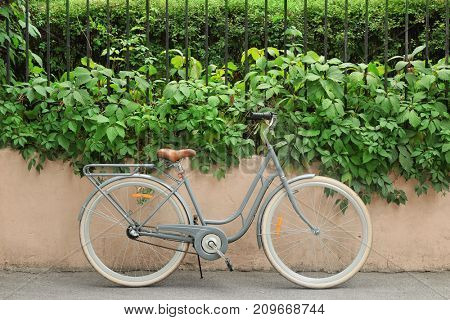 Retro bicycle near fence outdoors