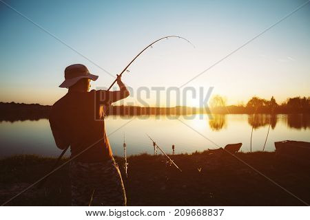 Men fishing in sunset and relaxing and enjoying hobby