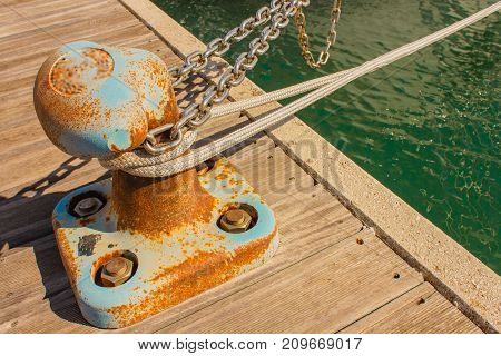 the bitt is a low cast-iron column in the shape of a mushroom to tie chains and mooring ropes /detail of a bitt with chains and ropes for mooring at the harbor