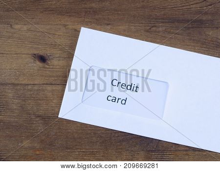 Letter on wooden table. Paper envelope with credit card inside