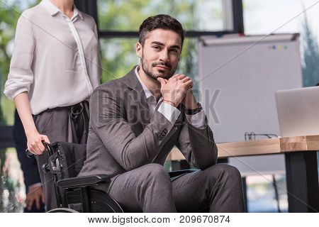 selective focus of smiling disabled businessman in wheelchair in office