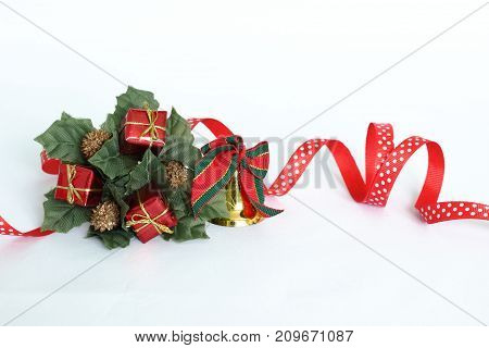Christmas decoration in the shape of a fir tree crown on a white background with a red ribbon, a golden bell, green leaves and red gifts