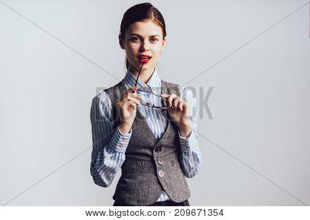 girl student holding in her hands her glasses posing on white background
