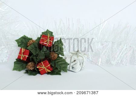 Green leaves and red gifts on a white background with a white garland for the holidays