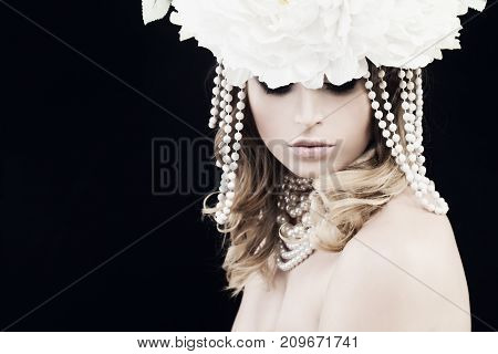 Gorgeous Woman with Pearls and White Flowers on Black Background