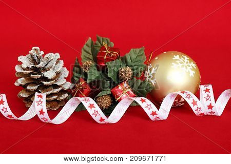 red gifts on a fir tree crown, a pine apple with snow on it and a golden ball for the decoration of parties on red background