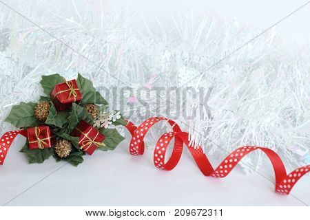 A frosted white  wreath with red ribbon and green leaves, red gifts on white background for party decoration