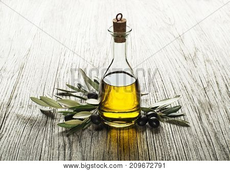 Olive oil and olive branch on a wooden background