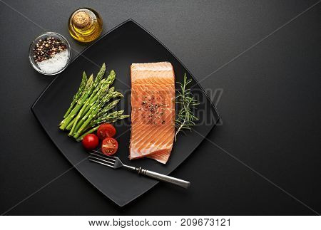 Raw steak of salmon with fresh ingredients on black background