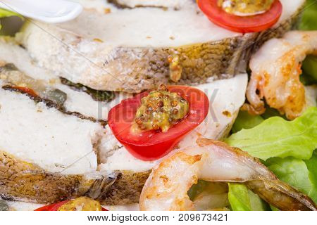 Stuffed seabass with shrimp and salad on plate