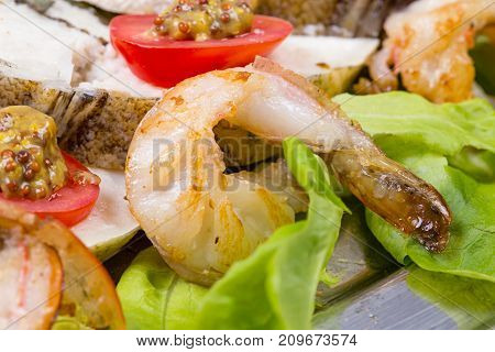 Stuffed seabass with fried shrimp and salad on plate