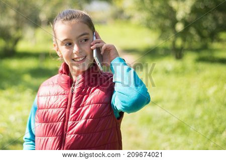 Beautiful girl talking on a smartphone in a red vest on the outdoor.Portrait smiles girl positive, emotion, happiness, smile. Young  girl receiving good news by phone. Portrait smiles girl
