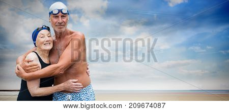 Smiling senior couple in swimwear embracing while standing against serene beach landscape