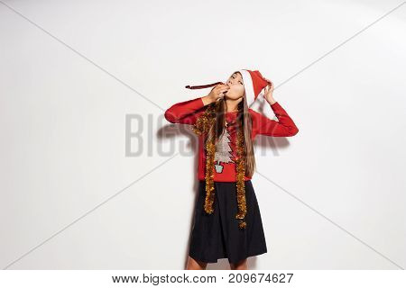a young sexy funny girl celebrates New Year and Christmas, in a red cap and a fashionable sweater with gold tinsel