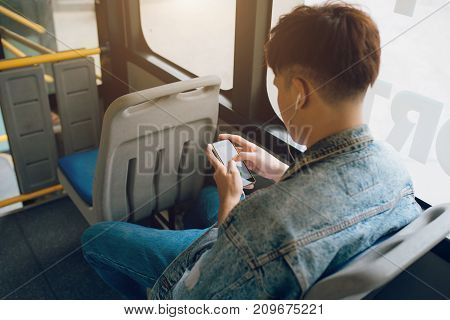 Handsome asian man sitting in city bus and sending message on the phone.