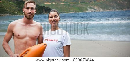 Portrait of confident lifeguards against sand at shore on sunny day