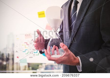 Mid section of businessman holding hourglass against adhesive notes on window